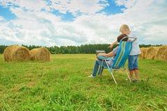 使用膝上型计算机的男孩和妇女坐干草 免版税图库摄影