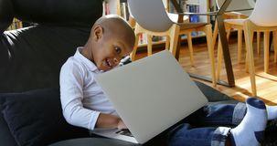 使用膝上型计算机的男孩在一个舒适的家4k 股票视频