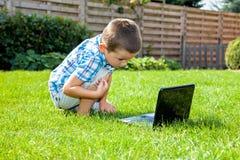 使用膝上型计算机的男孩室外 免版税库存照片
