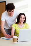 使用膝上型计算机的男性和女性大学生在教室 库存照片