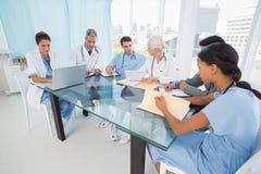 使用膝上型计算机的男性和女性医生 免版税库存照片