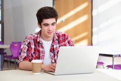 使用膝上型计算机的男性大学生在教室 免版税图库摄影