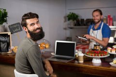 使用膝上型计算机的男性顾客,当喝咖啡在柜台在咖啡店时 免版税图库摄影