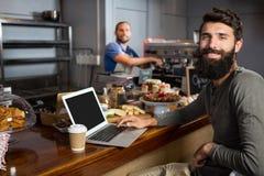使用膝上型计算机的男性顾客,当喝咖啡在柜台在咖啡店时 库存照片