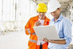 使用膝上型计算机的男性建筑师在建造场所 免版税库存图片
