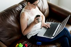 使用膝上型计算机的白人妇女在沙发 免版税库存照片