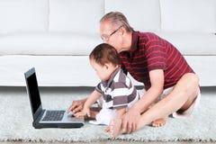 使用膝上型计算机的祖父和孙子 免版税库存图片