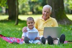 使用膝上型计算机的祖父和孩子 免版税库存照片