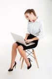使用膝上型计算机的繁忙的女实业家和谈话在电话 库存图片