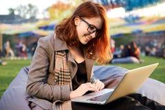 使用膝上型计算机的红头发人妇女在说谎在绿草的公园 图库摄影