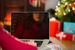 使用膝上型计算机的红头发人在圣诞节 免版税库存图片