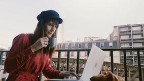 使用膝上型计算机的美丽的典雅的女实业家,享用咖啡在田园诗巴黎早晨阳台有埃菲尔铁塔视图 股票视频