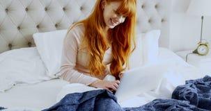 使用膝上型计算机的美丽的妇女,当放松在床4k上时 影视素材
