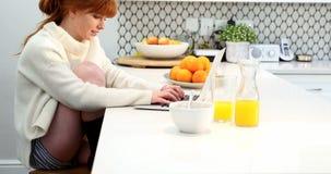 使用膝上型计算机的美丽的妇女,当食用早餐4k时 影视素材