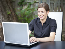 使用膝上型计算机的美丽的少妇外面 库存照片