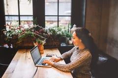 使用膝上型计算机的美丽的年轻深色的妇女在咖啡店在一张木桌在键盘的窗口键入的文本附近 在冬天, w 免版税库存照片