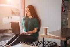 使用膝上型计算机的美丽的浅黑肤色的男人在咖啡馆 年轻可爱的妇女做计划为将来,坐在前面 免版税库存照片