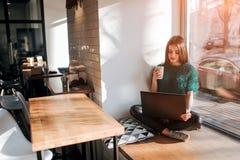 使用膝上型计算机的美丽的浅黑肤色的男人在咖啡馆 年轻可爱的妇女做计划为将来,坐在前面 库存照片
