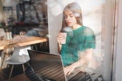 使用膝上型计算机的美丽的浅黑肤色的男人在咖啡馆 年轻可爱的妇女做计划为将来,坐在前面 库存图片