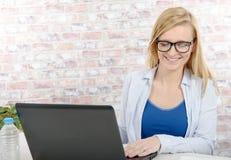 使用膝上型计算机的美丽的白肤金发的女商人 库存图片