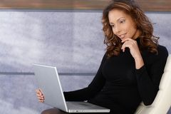 使用膝上型计算机的美丽的种族女性 免版税图库摄影