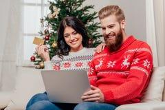 使用膝上型计算机的美好的夫妇,当坐在圣诞节时的沙发 免版税库存照片