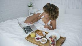 使用膝上型计算机的美满的妇女,当有膳食时 影视素材