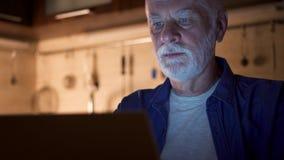 使用膝上型计算机的老人自由职业者在从家庭办公室的晚上 努力工作劳累过度的商人 影视素材