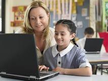 使用膝上型计算机的老师和女孩在类 图库摄影