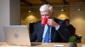 使用膝上型计算机的老白种人商人特写镜头射击和喝咖啡户内在工作场所的办公室 股票录像