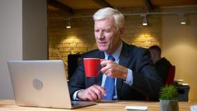 使用膝上型计算机的老白种人雇员特写镜头射击和喝咖啡户内在工作场所的办公室 股票视频