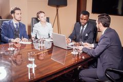 使用膝上型计算机的聪明的商务伙伴在会议上 库存图片