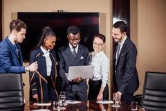 使用膝上型计算机的聪明的商务伙伴在会议上 免版税库存图片