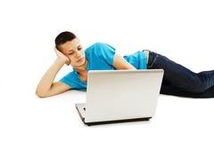使用膝上型计算机的英俊的十几岁的男孩 库存图片