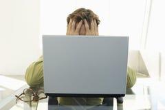 使用膝上型计算机的被注重的商人在办公室 库存图片