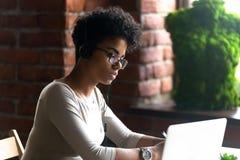 使用膝上型计算机的被聚焦的非裔美国人的妇女佩带的耳机 免版税库存照片