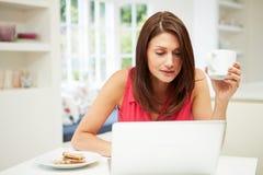 使用膝上型计算机的西班牙妇女在厨房 库存图片