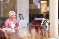 使用膝上型计算机的观点的资深妇女通过窗口 免版税库存图片
