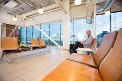 使用膝上型计算机的资深商人在机场大厅 免版税库存图片