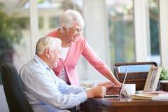 使用膝上型计算机的资深夫妇在书桌上在家 库存照片