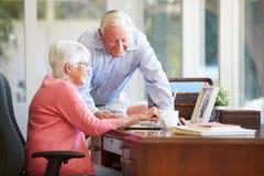 使用膝上型计算机的资深夫妇在书桌上在家 图库摄影
