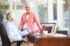 使用膝上型计算机的资深夫妇在书桌上在家 库存图片