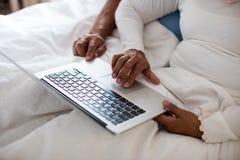 使用膝上型计算机的资深夫妇在卧室 免版税库存图片