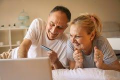 使用膝上型计算机的资深夫妇在床上 库存图片