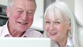 使用膝上型计算机的资深夫妇连接用家庭 股票视频