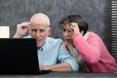 使用膝上型计算机的资深夫妇,他们有困难和视觉问题 免版税库存图片