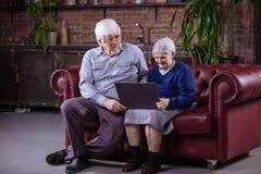 使用膝上型计算机的资深夫妇,当坐长沙发时 免版税库存照片
