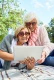 使用膝上型计算机的资深妇女在公园 库存照片
