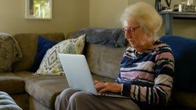 使用膝上型计算机的资深妇女在客厅 股票视频
