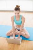 使用膝上型计算机的运动的快乐的妇女 图库摄影